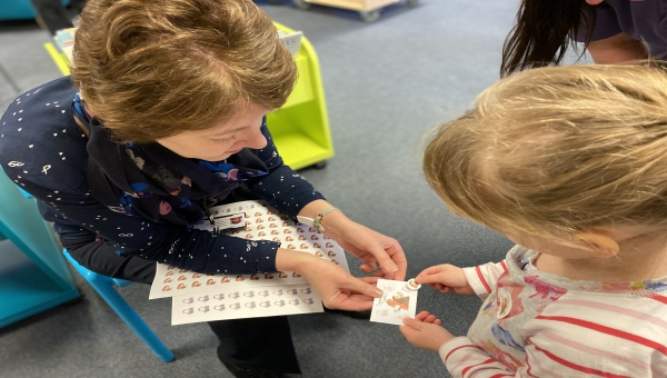 A child chooses a Squirrel Club sticker for her collector card