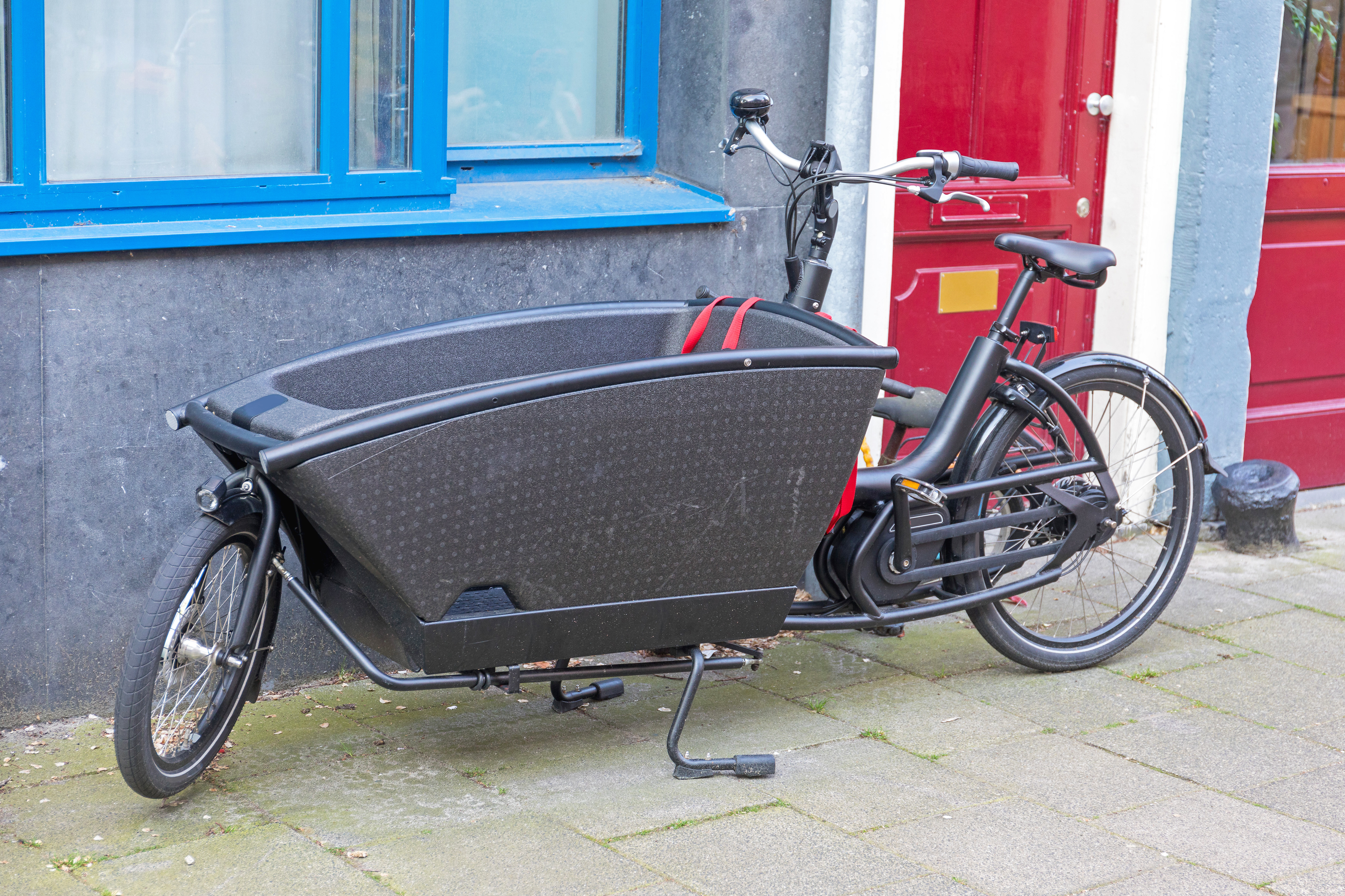 Adobe Stock photo of black electric cargo bike parked outside a building