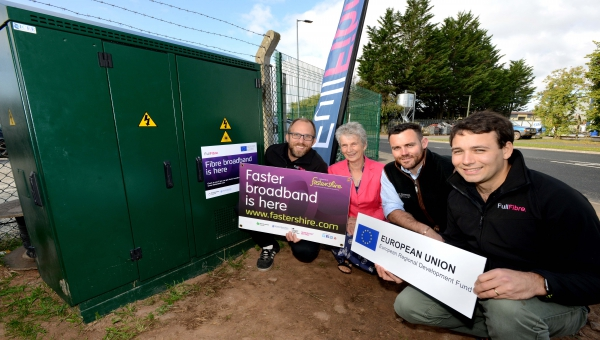 Councillor Trish Marsh and George Thomas, Director at G. P. Thomas Construction with Dan Jones and Oliver Helm from Full Fibre Limited crouched down next to a telephone exchange
