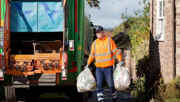 Bin man collecting recycling to place in bin lorry
