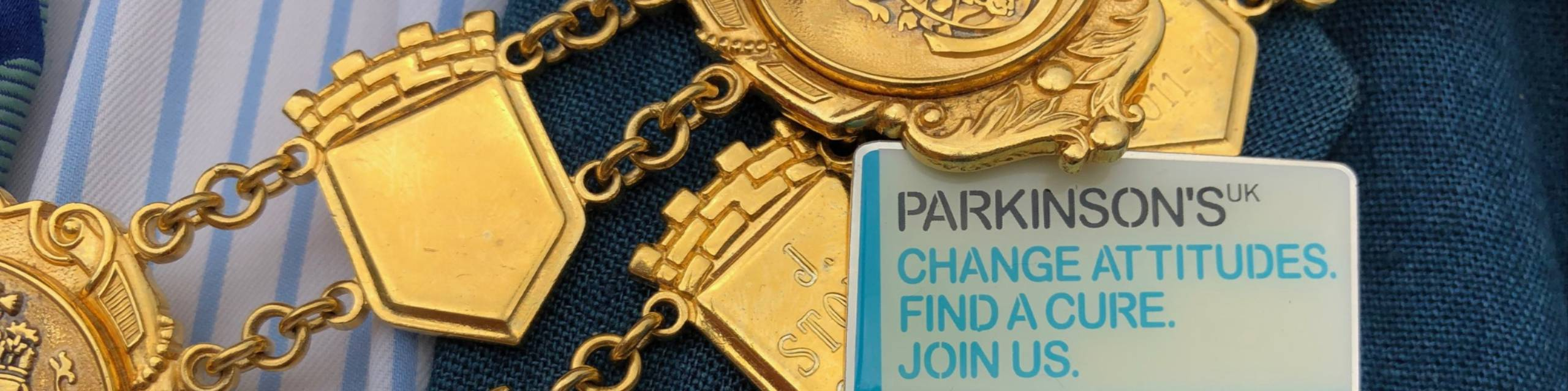 Parkinson's UK badge next to the Chairman's chains
