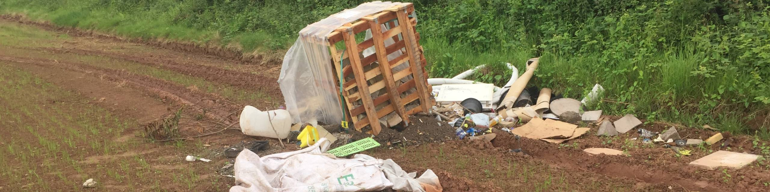 Business waste fly tipped in a field