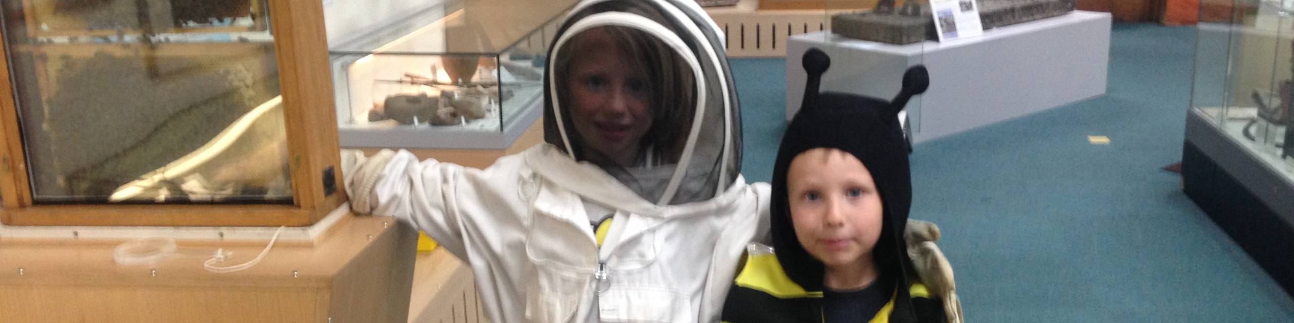 One child dressed in a beekeeper's costume and one child dressed as a bee