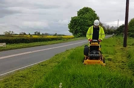 Cutting a grass verge beside a road
