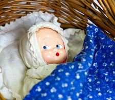 Image of doll in cot basket